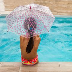 vacances d'été sous la pluie : fille au bord de la piscine sous la puie