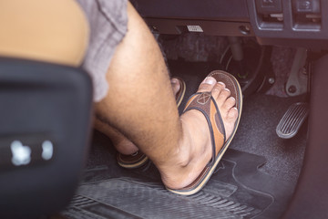Right foot with flip flop shoe step on the brakes in the modern car