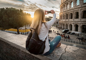 Woman tourist selfie with phone camera in hands near the Coliseu