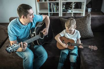 Father teaching his son to play on guitar at home. Son play on u
