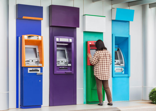 asian woman standing withdrawing money from banking machine or ATM(Automatic Teller Machine)