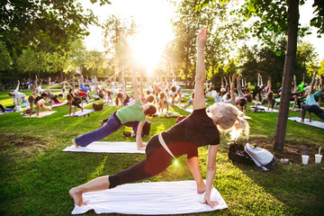 In de dag School de yoga big group of adults attending a yoga class outside in park
