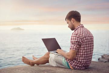 Mann mit Laptop sitzt am Meer Wall mural