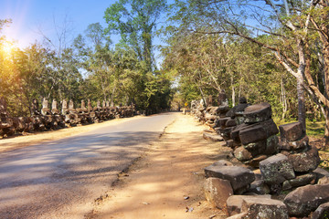 road to temple and ruins of statues, 12th century, Cambodia..
