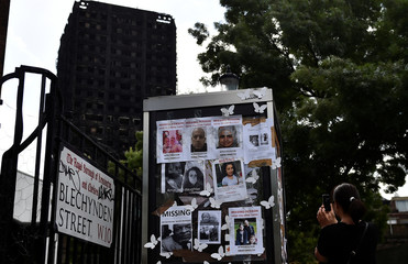A woman photographs missing persons posters near the scene of the fire that destroyed the Grenfell Tower block, in north Kensington, West London