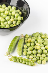 Fresh raw green peas in the bowl isolated over white background