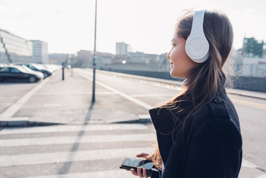Side view young woman walking in the city back light listening music headphones with smart phone hand hold - music, relaxing, enjoyment concept