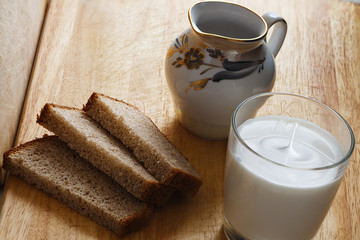 A glass of milk with bread and a jug on a wooden table with light from a window