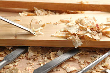 Working with chisel and wooden board in carpenter's shop, closeup