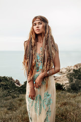 beautiful young boho girl on a hill with sea background