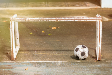 Old soccer ball on the cement floor.