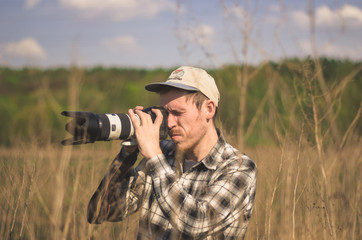 A hipster photographer takes photos in the countryside