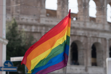 Berlin, Germany - June 10, 2017: Gay pride day, big rainbow flag fluttering against the Colosseum. Gay pride or LGBT pride is the positive stance against discrimination and violence toward LGBT people