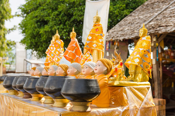 Buddha statues on table with alms bowls