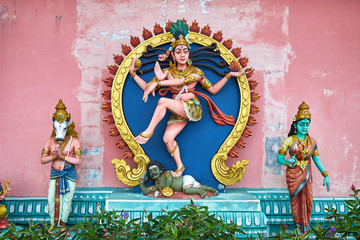 Hindu god Shiva as Lord of the Dance (Nataraja) statue in hindu temple with Nandi and Parvati on the sides