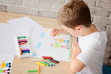 Child draws a drawing of happy son and father