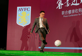 Recon Group CEO Tony Xia kicks a ball during a news conference for Recon GroupÄôs acquisition of soccer club Aston Villa in Beijing