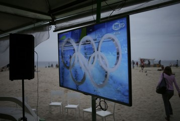 A television screen shows swimming competition on Copacabana Beach in Rio