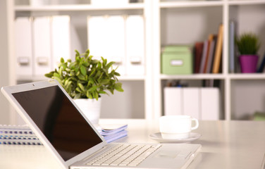 Close up view of a work desk interior with a laptop computer, a cup of coffee and white curtains on a sunny day