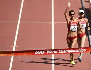Liu Hong of China (L) celebrates on her way to the finish line as she wins the women's 20 km race walk final ahead of Lu Xiuzhi of China during the 15th IAAF World Championships at the National Stadium in Beijing