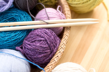 Set of colored yarn balls and needles on straw plate close up, wooden table as a background