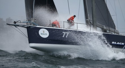 Crew members aboard the yacht Blackjack are hit by ocean swells  during the 71st Sydney to Hobart Yacht race