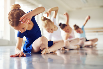 Foto auf AluDibond Tanzschule Girls bending sitting on floor in ballet class