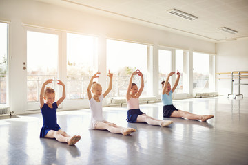 Group of little ballerinas with hands up sitting on floor