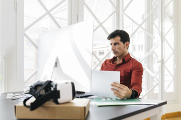 Spain, Barcelona. Business man working at office with computer, graph data documents on his desk.