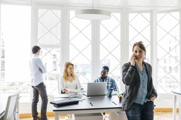 Spain, Barcelona. Portrait of a woman speaking with mobile in the office startup with colleagues in the background