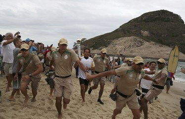 Brazilian surfer Rico de Souza carries the Olympic torch after surfing with it at praia da Macumba (Macumba beach) in Rio de Janeiro   , Brazil