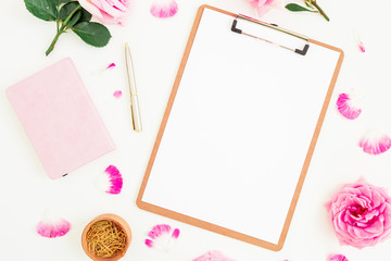 Minimalistic workspace with clipboard, pink roses, notebook and pen on white background. Flat lay, top view.