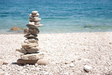 Horizontal image of tall zen tower made of grey stones on white each with blue sea in the background