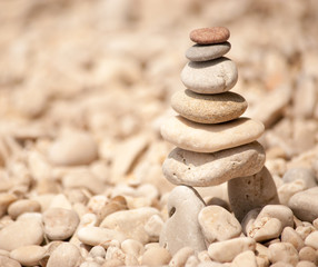 Zen tower of six stones stacked on stilts on a pale pebble beach, square image