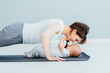 young mother does physical yoga exercises together with her baby boy