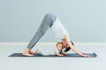 In de dag School de yoga young mother does physical yoga exercises together with her baby boy