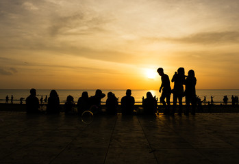Silhouettes of people enjoying sunset at Tanjung Aru beach Sabah Borneo.