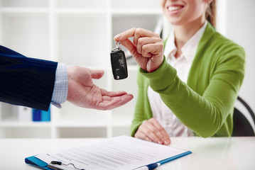Car rent or sale. Rental agent giving automobile key to customer in the office.