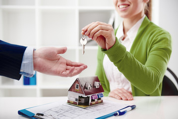 Real estate agency. Woman broker offering key of new house to male client.