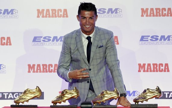 Real Madrid's striker Cristiano Ronaldo poses in front of his four Golden Boot trophies during a ceremony in Madrid, Spain