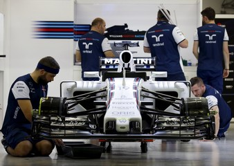 Crew members work on the car of Williams Formula One driver Felipe Massa of Brazil in the pit ahead of the Singapore F1 Grand Prix night race in Singapore