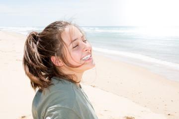 smiling happy cute teenager girl in ocean sea beach