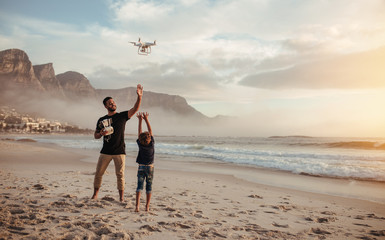 Father and son flying drone with remote control at beach