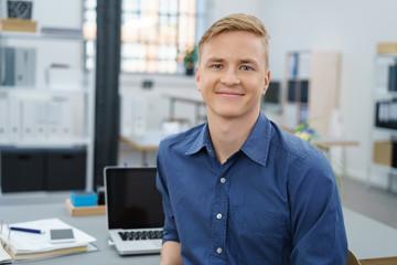lächelnder junger geschäftsmann im büro