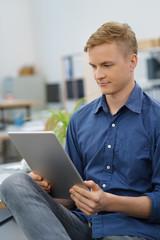 junger mann liest am tablet