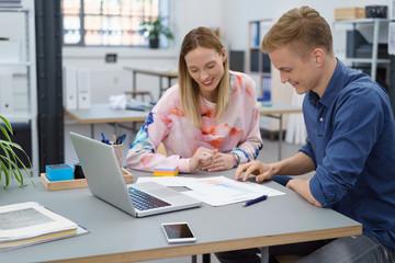 junge mitarbeiter unterhalten sich im büro und schauen auf unterlagen