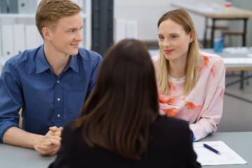 junges paar in einem beratungsgespräch bei der bank oder versicherung
