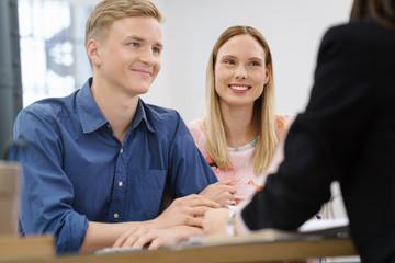 glückliches junges paar in einem beratungsgespräch