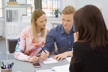 junges paar macht sich notizen in einem beratungsgespräch