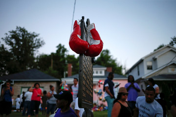 Boxing gloves hang from a marker outside childhood home of  late boxing champion Muhammad Ali in Louisville, Kentucky, U.S.